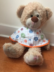 teddy bear wearing aden+ anais burp cloth bib as bib