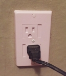 KidCo self closing outlet cover installed on wall with cord plugged in