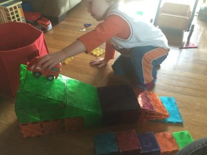 Child rolling car down ramp built from magnetic tiles