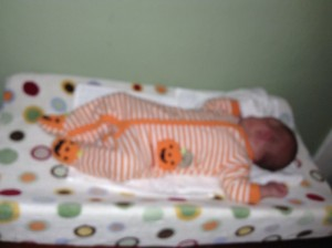 Infant in orange striped pajamas with pumpkin feet on a changing pad with polka dot cover