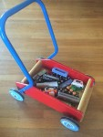 Walker wagon red sides blue handle and blue wheels with white spirals filled with wooden trains