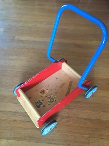 Empty walker wagon with blue handle blue wheels and red sides with stickers stuck to bottom