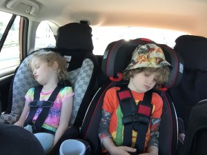 Child sleeping in Graco Nautilus 80 Elite 3 in 1 booster seat in car next to child sleeping in Britax Roundabout convertible car seat