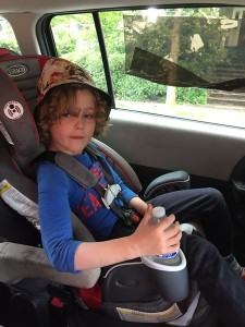 Child shown buckled into the five point harness of the Graco Nautilus 80 Elite 3 in 1 booster seat