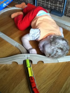 Toddler laying down to play with IKEA wooden train set