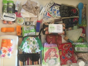 Contents of diaper baby changing bag laid out on flat surface