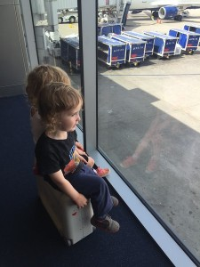 Two kids sharing a seat on a JetKids BedBox at the airport