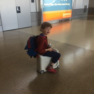 Six year old riding on a JetKids BedBox ride on suitcase