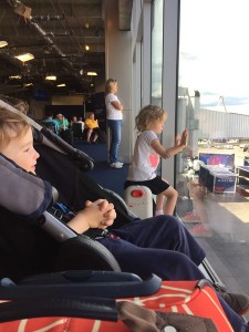 Five year old sitting at window at the airport gate on a JetKids BedBox