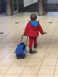 A toddler in a red winter jacket pulling a Popatu blue airplane wheeled suitcase through the airport