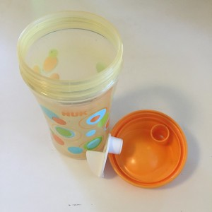 An open Nuk ultimate hard spout sippy cup showing the three parts: cup, lid, and valve