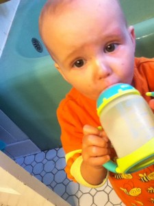 Toddler drinking milk from Nuk soft spout sippy cup with handles