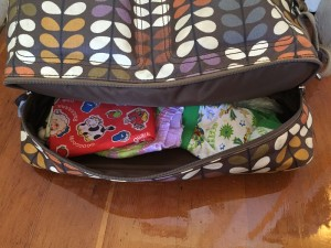 Bottom compartment of Orla Kiely baby diaper changing bag shown unzipped with diaper supplies inside