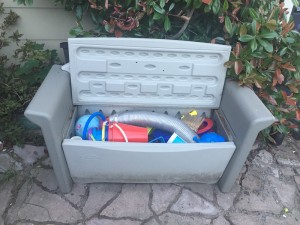 Rubbermaid outdoor patio storage bench shown open filled with outdoor toys