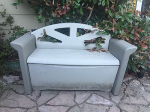 Rubbermaid outdoor patio storage bench shown in yard with lid closed