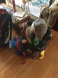 A child raising the handle on his Yodo kids rolling backpack suitcase