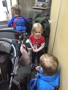 Three kids carrying small suitcases on a jetway