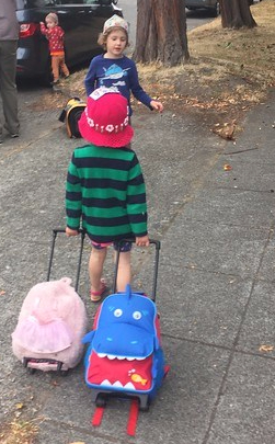 Child pulling two kid suitcases, a pink fuzzy one from Popatu and a blue shark one from Yodo
