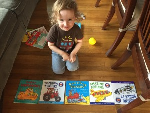 Toddler with five titles from Amazing Machines paperback book series by Tony Mitton laid out on floor
