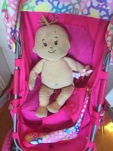 Baby Stella by Manhattan Toy riding in a doll stroller