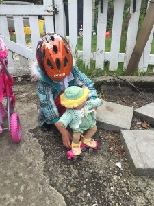 Child playing with Baby Stella doll by Manhattan Toy on roller skates