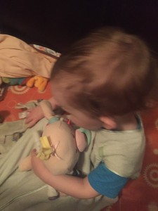 Toddler snuggling a Baby Stella doll by Manhattan Toy