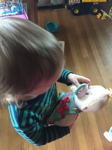 Toddler playing with Baby Stella doll and pacifier by Manhattan Toy