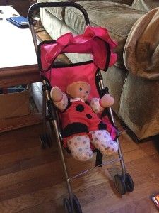 Baby Stella ladybug costume clothes on soft doll in stroller