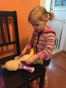 Preschooler child changing clothes on Baby Stella doll by Manhattan Toy