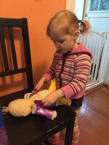 Preschooler child changing clothes on Baby Stella doll by Manhattan Toy