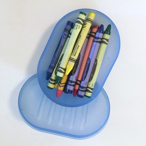 Blue translucent soap dish opened to show crayons stored inside