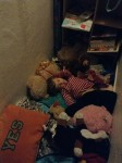 Child asleep in closet surrounded by stuffed animals and toys