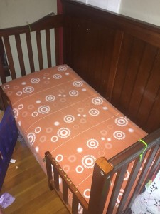 Olli and Lime Billie crib sheet shown in crib converted to toddler bed