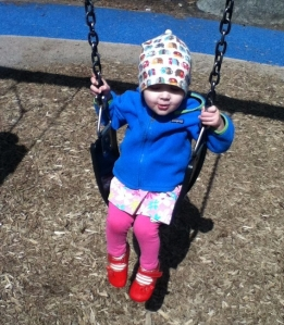 Child swinging while wearing a Patagonia fleece hooded full zipper jacket