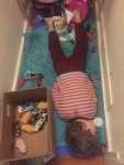 Six year old passed out on rug in hall among scattered toys