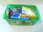 Child art supplies like crayons stored in am empty disposable wipes container
