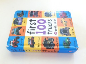 First 100 Trucks board book by Roger Priddy laying on its side