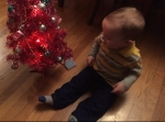 Baby in fleece pants sitting next to small pink Christmas tree