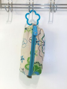 Zip up bag in green and blue floral pattern on white background hanging from infant toy link