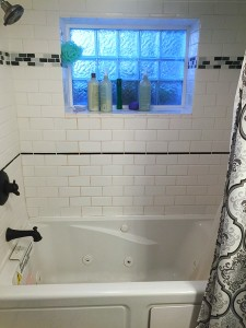Bathtub and shower with white tile and black and gray accent colors shown with curtain open