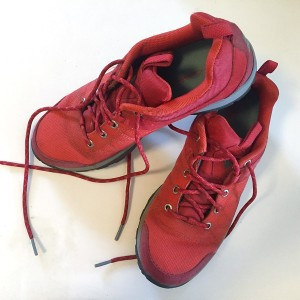 Red Columbia sneakers tennis shoes with laces undone on white background