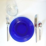 Blue glass plate with silverware and clear glass plate setting