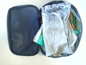 Eagle Creek Pack It Medium cube shown open unzipped and filled with kid clothes