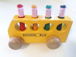 Wooden yellow school bus with painted stick people that pop up