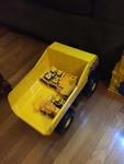 Tonka Mighty Steel dump truck in bright yellow and black carrying other smaller construction toys