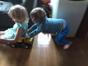 Preschooler pushing five year old in Tonka steel dump truck