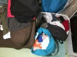 Piles of laundry shown in bag, basket, and draped across furniture