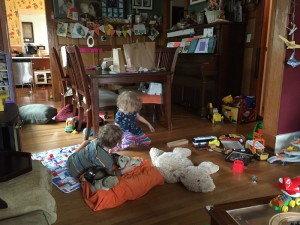 Dining room shown covered in stuff with toys scattered over floor with two kids playing