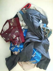 Kid's dirty clothes in small pile turned inside out with one clean article right side out