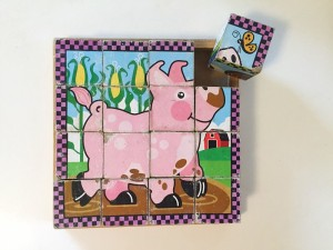 Melissa and Doug Wooden Cube puzzle pig farm animal completed with one block tipped out of storage tray